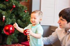 Сын и папа украшая рождественскую елку дома в живущей комнате Стоковые Фотографии RF