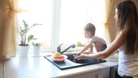 Сын мальчика помогает маме в кухонной раковине акции видеоматериалы