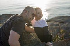 Сын на отце взваливает на плечи на пляж имея заход солнца потехи совместно стоковая фотография