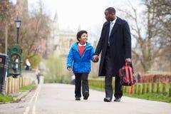 Сын отца идя к школе вдоль пути стоковая фотография