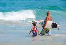 Сын отца уча как к серфингу стоковые фотографии rf