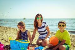 Сын дочери матери семьи имея потеху на пляже Стоковые Изображения