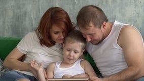 Сын показывает интересное в таблетке к родителям Люди с технологией сток-видео