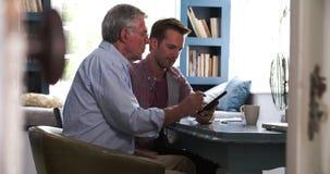 Сын помогая старшему отцу с таблеткой цифров дома сток-видео