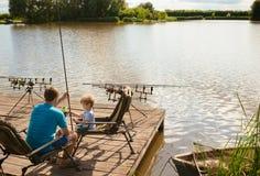 Сын преподавательства отца, который нужно удить на береге озера стоковые фотографии rf