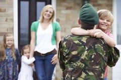 Сын приветствуя воинского отца на разрешении дома стоковые фотографии rf