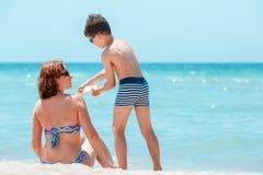 Сын прикладывая сливк sunblock на его плече матери стоковое фото