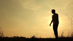 Сын семьи silhouetted прогулкой отбрасывая