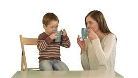Сын с его чаем матери выпивая на белой изолированной предпосылке Стоковое фото RF