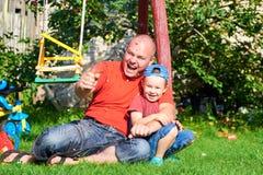 Сын с его шутихой дунутой отцом бумажной Стоковое фото RF