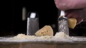 Сыра решетка медленно на терке металла на деревянном столе Следующий пук заскрежетанного сына ( Ingred концепция варить акции видеоматериалы