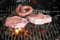 Сырое мясо и сосиска на барбекю жарят, крупный план Стоковая Фотография RF