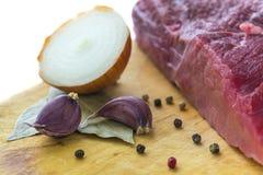 Сырое мясо на борту с половиной гвоздичных деревьев лука и чеснока закрывает Стоковые Изображения RF