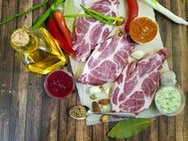 Сырое мясо на деревянной доске перца, масло, соус, гайки, chili, лимон, перец залива, чеснок, натуральные продукты Стоковое фото RF