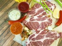 Сырое мясо на деревянной доске перца, масло, соус, гайки, chili, лимон, перец, чеснок, натуральные продукты Стоковое Фото