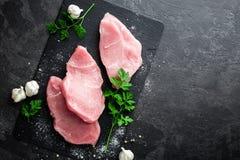 Сырое мясо, стейки индюка на черной предпосылке, взгляд сверху Стоковые Фото