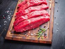 Сырое мясо, стейк говядины с приправой на прерывая доске на темном ба стоковая фотография
