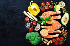 Сырое salmon филе рыб с ароматичными травами, лук, авокадо, брокколи, колокол перца, овощи на темной предпосылке стоковые фото