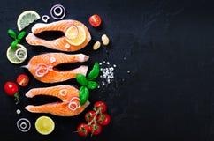 Сырое salmon филе рыб с ароматичными травами, лук, авокадо, брокколи, колокол перца, овощи на темной предпосылке стоковое изображение rf