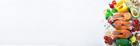 Сырое salmon филе рыб с ароматичными травами, лук, авокадо, брокколи, колокол перца, овощи на белой предпосылке стоковое фото rf
