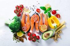 Сырое salmon филе рыб с ароматичными травами, лук, авокадо, брокколи, колокол перца, овощи на белой предпосылке стоковая фотография rf