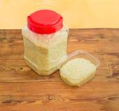 Сырой рис в 2 различных больших и малых пластмасовых контейнерах Стоковые Изображения RF