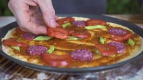 Сырцовая итальянская пицца с томатами, сосиской pepperoni и зелеными фасолями на таблице Руки Pizzaillo делая пиццу на итальянско сток-видео