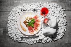 Сырцовая и посоленная ветчина, голубой сыр и базилик и одиночное стекло красного вина на белом камне и на деревянной предпосылке Стоковые Фото