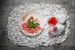 Сырцовая и посоленная ветчина, голубой сыр и базилик и одиночное стекло красного вина на белом камне и на деревянной предпосылке Стоковая Фотография RF