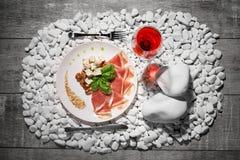 Сырцовая и посоленная ветчина, голубой сыр и базилик и одиночное стекло красного вина на белом камне и на деревянной предпосылке Стоковая Фотография