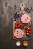 Сырцовая котлета для бургеров, с томатами вишни и травами на разделочной доске, пансионер, космос для верхней части предпосылки т стоковые фото