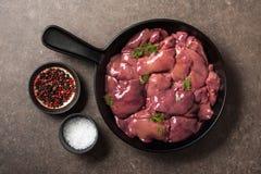 Сырцовая куриная печень в сковороде, соли и перце на tabl кухни Стоковые Фото