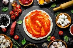 Сырцовая пицца Свернутое вне тесто с томатной пастой, сосиской, моццареллой и оливками стоковое фото rf