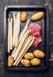 Сырцовая спаржа с шницелем мяса телятины и картошками yong на черном подносе затыловки стоковое фото