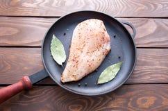 Сырцовое свежее филе куриной грудки с травами и специями и лист залива готово для варить, в черной сделанной сковороде стоковые изображения rf