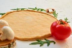 Сырцовое тесто пиццы на белой предпосылке с космосом бесплатной копии Тесто с ингридиентами для вегетарианской пиццы: грибы, тома Стоковое Фото