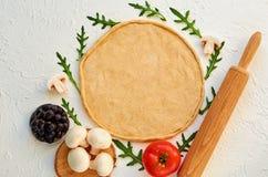 Сырцовое тесто пиццы на белой предпосылке с космосом бесплатной копии Тесто с вращающей осью и ингридиентами для вегетарианской п Стоковая Фотография