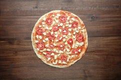 Сырцовое тесто пиццы с томатами и моццареллой на деревянной предпосылке Стоковое Изображение