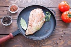 Сырцовое филе цыпленка взбрызнутое с травами и специями готовыми для того чтобы сварить лож на сковороде черного листового железа стоковое изображение rf