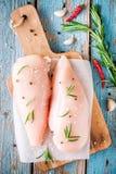 Сырцовое филе цыпленка с чесноком, перцем и розмариновым маслом на деревенской предпосылке Стоковые Фотографии RF