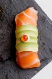 Сырцовое Salmon отбензинивание суш при авокадо и косули Ikura, который Salmon служат на черной каменной плите Стоковое фото RF