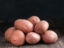 Сырцовые все органические картошки на старой деревянной предпосылке Стоковая Фотография