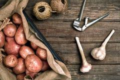 Сырцовые все помытые органические картошки и чеснок на дерюге над старой деревянной предпосылкой планки Взгляд сверху с космосом  Стоковое Изображение RF