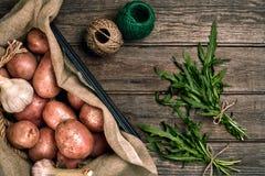 Сырцовые все помытые органические картошки, чеснок и ruccola на дерюге над старой деревянной предпосылкой планки Взгляд сверху с  Стоковая Фотография RF