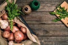 Сырцовые все помытые органические картошки, чеснок и ruccola на дерюге над старой деревянной предпосылкой планки Взгляд сверху с  Стоковые Фото
