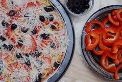 Сырцовые домодельные пицца и ингридиенты с красным перцем и черными оливками на белом деревянном столе Стоковые Изображения