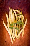Сырцовые желт-зеленые стручковые фасоли на поверхности темного коричневого цвета деревянной Стоковые Фото