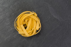Сырцовые желтые макаронные изделия tagliatelle на плите шифера Стоковая Фотография RF