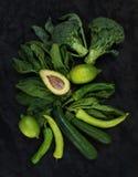 Сырцовые зеленые установленные овощи Брокколи, авокадо, перец, шпинат, цукини, известка на темной каменной предпосылке Стоковые Фотографии RF