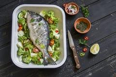 Сырцовые ингридиенты - рыбы и овощи Dorado - брокколи, цукини, луки, перцы, известка и специи на темной деревянной поверхности Стоковые Фотографии RF
